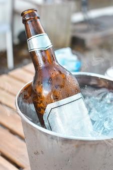 Botella de cerveza en cubo de hielo