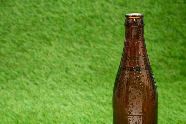 Botella de cerveza con fondo de hierba y espacio de copia
