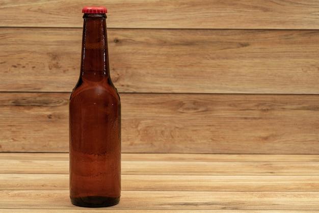 Botella de cerveza con fondo de madera
