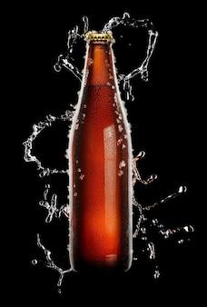 Botella de cerveza marrón fría con gotas de agua y hielo sobre negro