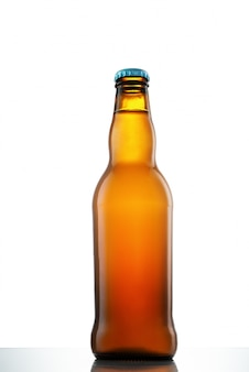 Botella de cerveza en una mesa de cristal blanco sobre blanco aislado