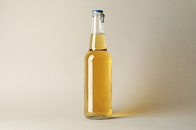 Botella de cerveza sobre fondo gris, espacio para texto