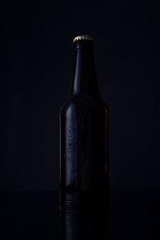 Botella de cerveza sobre fondo negro botella de cerveza sobre un fondo negro. foto publicitaria