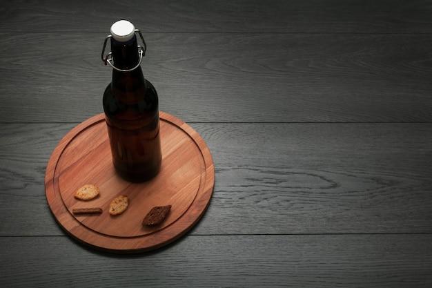 Botella de cerveza en tabla de cortar con espacio de copia