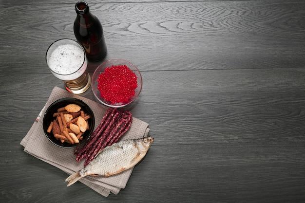 Botella de cerveza y vaso con comida y espacio de copia