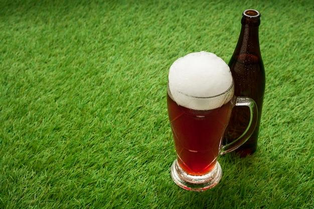 Botella de cerveza y vidrio sobre hierba con espacio de copia