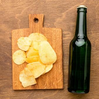 Botella de cerveza vista superior con patatas fritas en la tabla de cortar