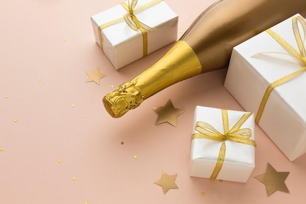 Botella de champagne de alto ángulo con regalos