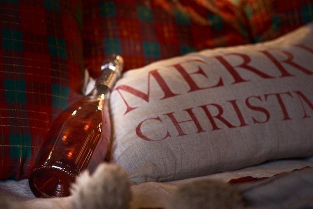 Botella de champagne en la cama. fiesta de navidad. almohada con la inscripción feliz navidad.