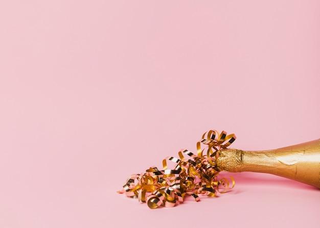 Botella de champagne con cintas y copia espacio fondo rosa