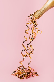 Botella de champagne y cintas doradas.
