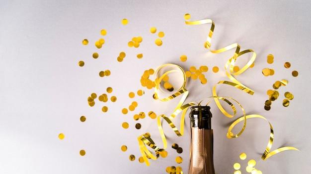Botella de champagne con confeti dorado y serpentinas sobre fondo blanco.