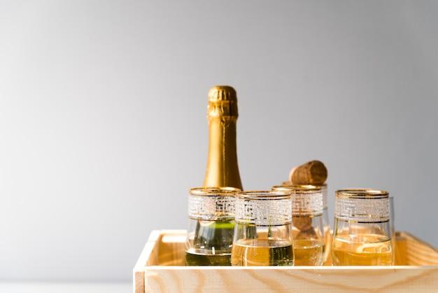Botella de champagne y copas en cajón de madera sobre fondo blanco.