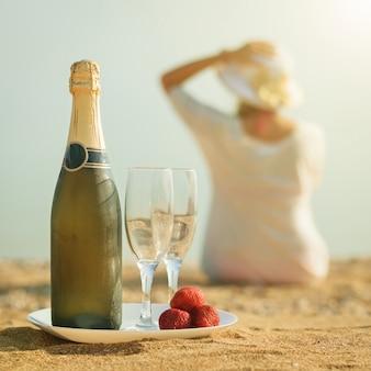 Una botella de champagne, copas y fresas.