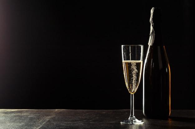 Botella de champagne y copas sobre fondo oscuro