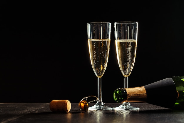 Botella de champagne y copas sobre oscuro