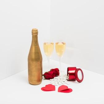 Botella de champagne con corazones de papel.