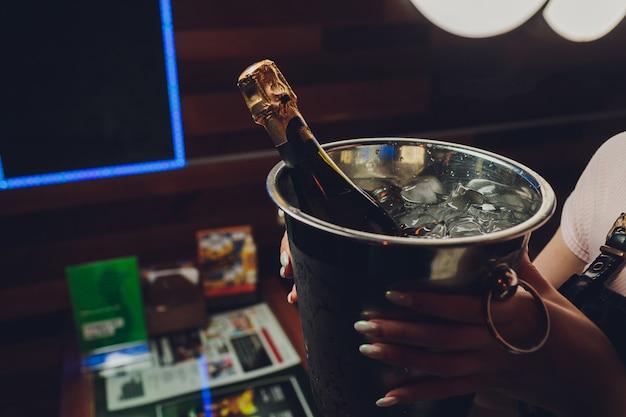 Botella de champagne en un cubo con hielo en la oscuridad.