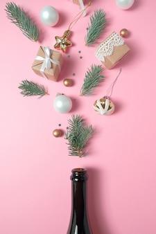 Botella de champagne con diferentes decoraciones de navidad sobre fondo rosa. concepto de año nuevo