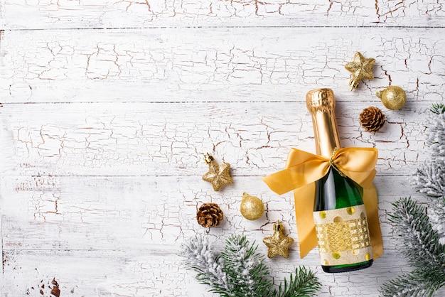 Botella de champagne en una envoltura de oro con decoración navideña.