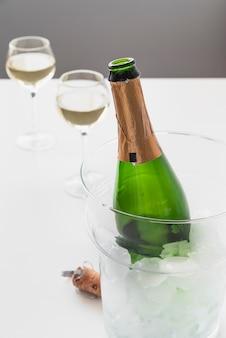 Botella de champagne con hielo y vasos.