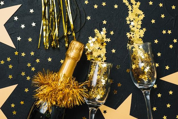 Botella de champagne con lentejuelas en copas en mesa