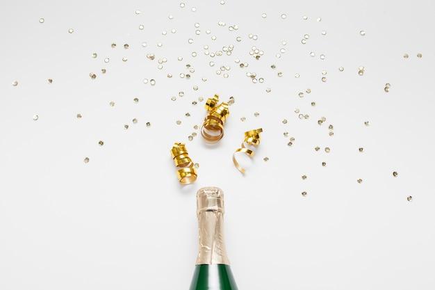 Botella de champagne con purpurina y confeti.