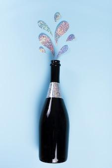 Botella de champagne con salpicaduras de purpurina.