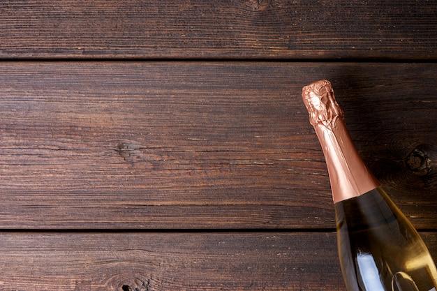Una botella de champagne sobre fondo de madera.