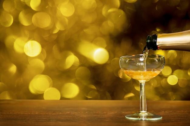 Botella de champagne vertiendo en copa con efecto bokeh