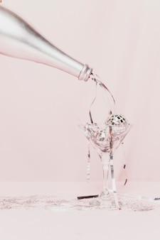 Botella de champagne vertiendo oropel en vidrio