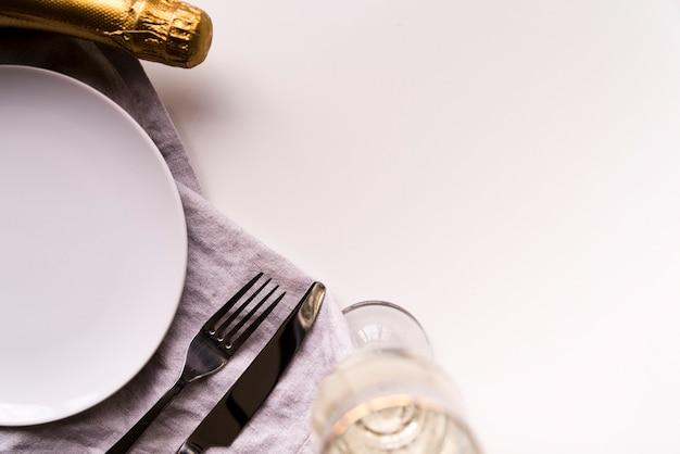 Botella de champagne y vidrio con plato vacío sobre fondo blanco.