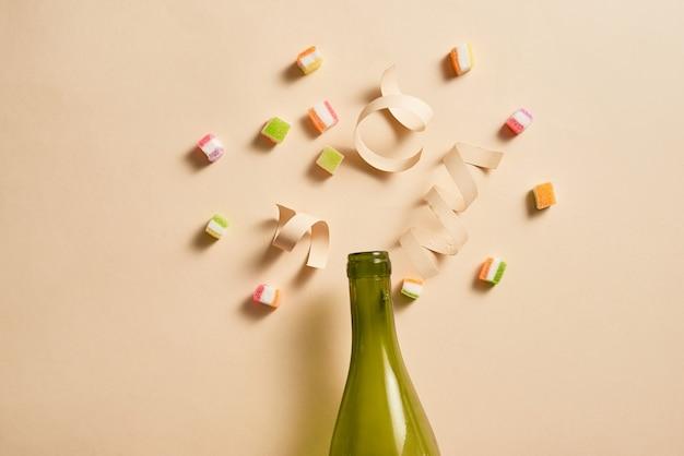 Botella de champán con coloridos artículos de fiesta.