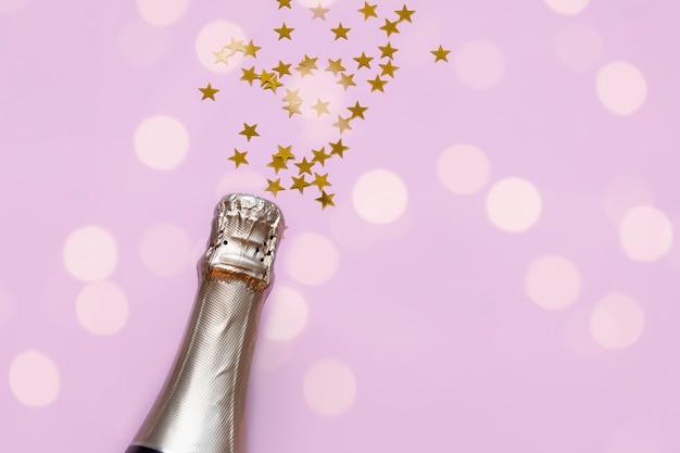 Botella de champán con confeti de estrellas doradas sobre un fondo rosa pastel y luces bokeh con copyspace