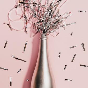 Botella de champán con confeti en fiesta de año nuevo