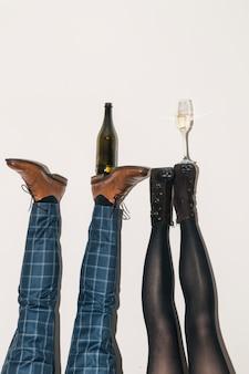 Botella de champán y copa en los pies.
