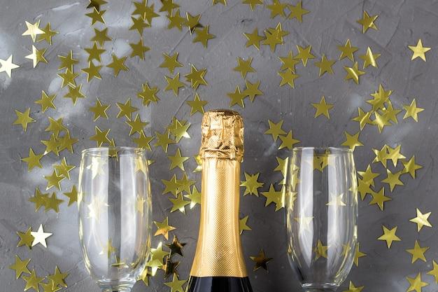 Botella de champán y copas con estrellas de confeti dorado. concepto para navidad, año nuevo, cumpleaños o boda.