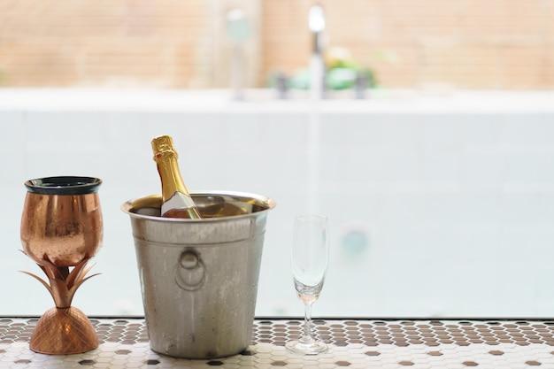 Botella de champán en un cubo de hielo y dos copas cerca de la piscina de burbujas
