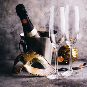 Botella de champán en un cubo con hielo, vasos y adornos navideños.
