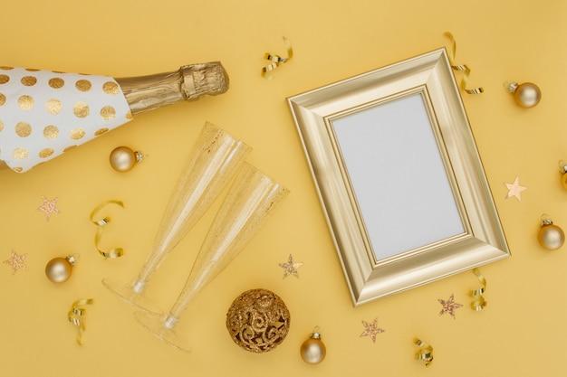 Botella de champán y decoración con maqueta de marco