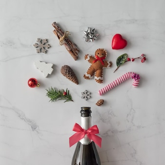 Botella de champán con decoración navideña en la pared de mármol. endecha plana. concepto de fiesta.