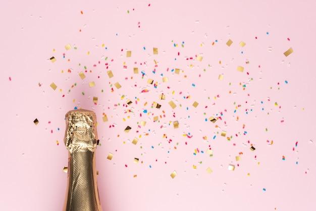 Botella de champán dorado con confeti sobre fondo rosa.