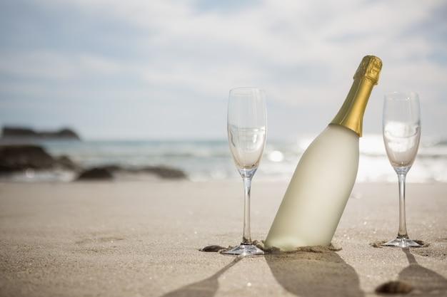 Botella de champán y dos copas en la arena
