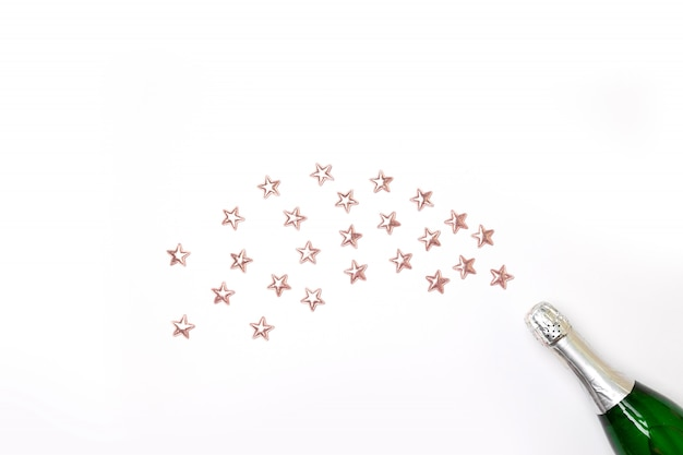 Botella de champán con estrellas de confeti y serpentinas de fiesta en rosa