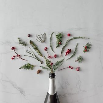 Botella de champán con follaje de invierno en la pared de mármol. endecha plana. concepto de fiesta.