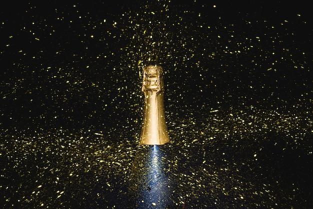 Botella de champán con lentejuelas que caen.