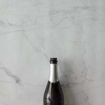 Botella de champán en la pared de mármol. endecha plana. concepto de fiesta.