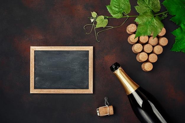 Botella de champán, racimo de corcho con hojas y pizarra sobre fondo oxidado