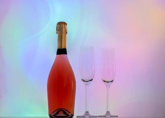 Botella de champán rosa rosa y dos copas emty sobre fondo colorido.