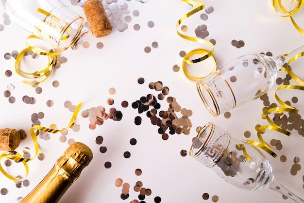 Botella de champán con vasos vacíos; confeti y serpentinas sobre fondo blanco.